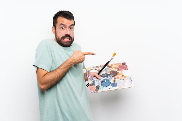 Przestraszony młody artysta trzyma paletę nad izolowaną ścianą i wskazuje na bok