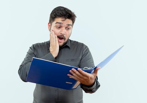 Przestraszony młody biznesmen gospodarstwa i patrząc na folder i kładąc rękę na policzku na białym tle