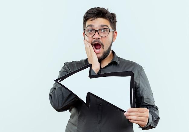 Przestraszony młody biznesmen w okularach posiadających znak kierunku na białym tle z miejsca kopiowania