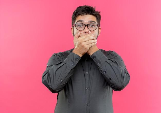 Przestraszony młody biznesmen w okularach zakryte usta rękami odizolowane na różowo