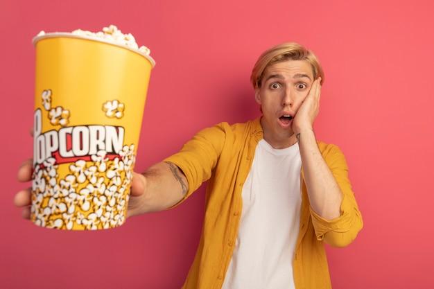 Przestraszony młody blondyn ubrany w żółtą koszulkę trzyma wiadro popcornu