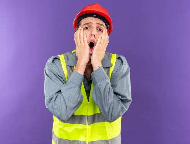 Przestraszony młody budowniczy mężczyzna w mundurze, kładąc ręce na policzkach