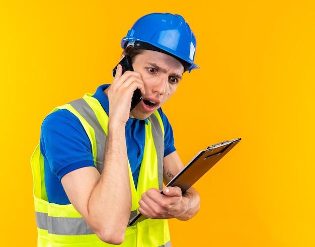 Przestraszony młody budowniczy mężczyzna w mundurze trzymającym schowek mówi przez telefon