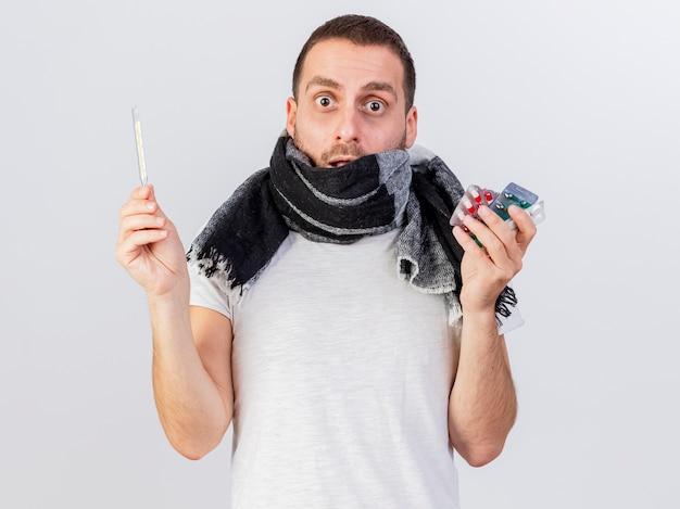 Przestraszony młody chory człowiek ubrany w szalik zawinięty w kratę trzymając pigułki z termometrem na białym tle