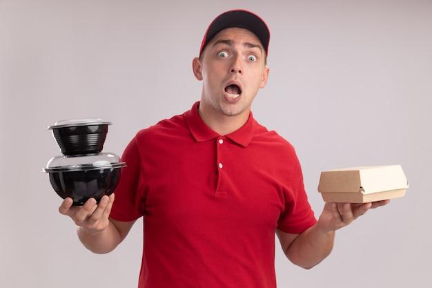 Przestraszony młody człowiek dostawy ubrany w mundur z czapką trzymając papierowy pakiet żywności z pojemnikiem na żywność na białej ścianie