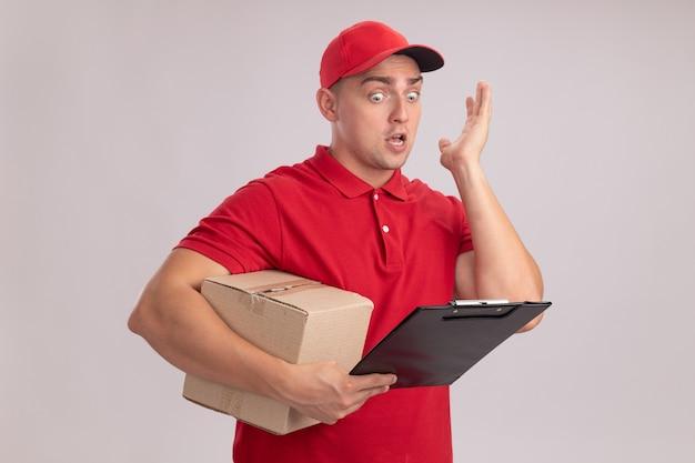 Przestraszony młody człowiek dostawy ubrany w mundur z czapką, trzymając pudełko i patrząc na schowek w ręku na białym tle na białej ścianie