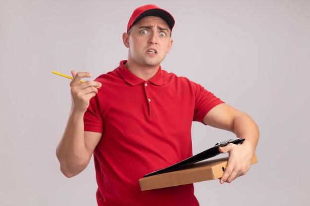 Przestraszony młody człowiek dostawy ubrany w mundur z czapką, trzymając pudełko po pizzy ze schowka na białym tle na białej ścianie