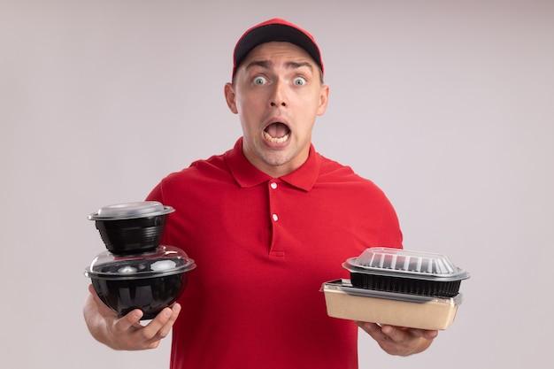 Przestraszony młody człowiek dostawy ubrany w mundur z czapką trzymającą pojemniki na żywność na białej ścianie