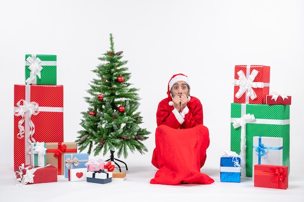 Przestraszony młody człowiek przebrany za świętego mikołaja z prezentami i ozdobioną choinką siedzi na ziemi na białym tle