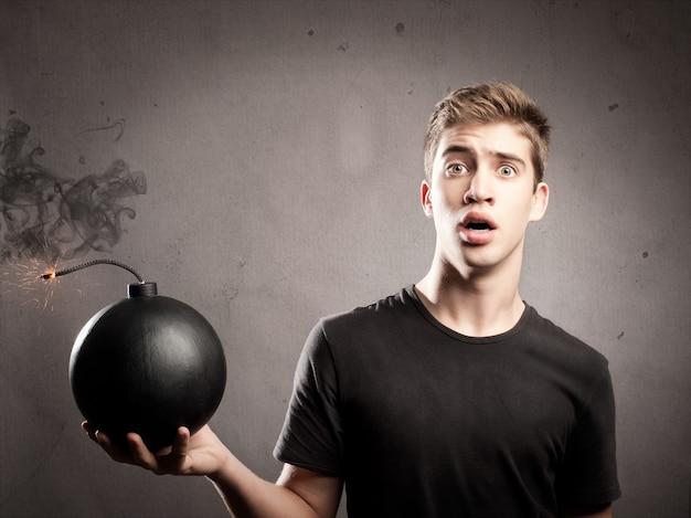 Przestraszony młody człowiek trzyma staromodną bombę