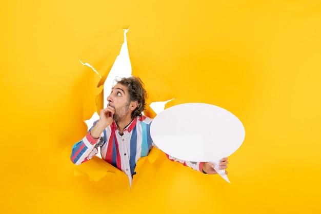 Przestraszony młody człowiek wskazujący białą stronę z wolną przestrzenią w rozdartej dziurze w żółtym papierze