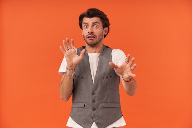 Przestraszony młody człowiek z zarostem trzyma ręce przed sobą i wygląda na przerażonego