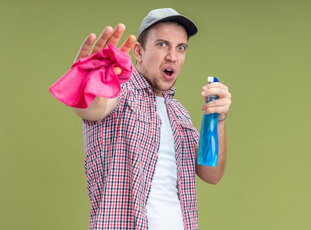 Przestraszony młody facet sprzątacz w czapce trzymającej środek czyszczący ze szmatą pokazując dobry gest na oliwkowym tle