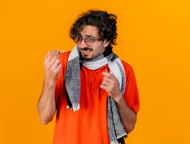 Przestraszony młody kaukaski chory mężczyzna w okularach i szaliku trzymający strzykawkę i ampułkę patrząc na strzykawkę odizolowaną na pomarańczowej ścianie z miejscem na kopię
