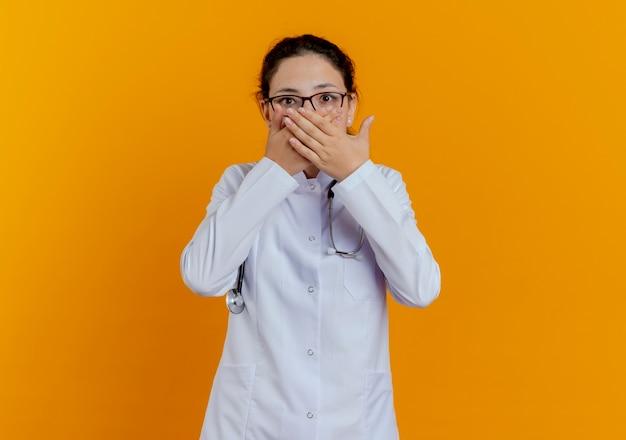 Przestraszony młody lekarz kobiet na sobie fartuch medyczny i stetoskop w okularach zakrytych rękami usta na białym tle
