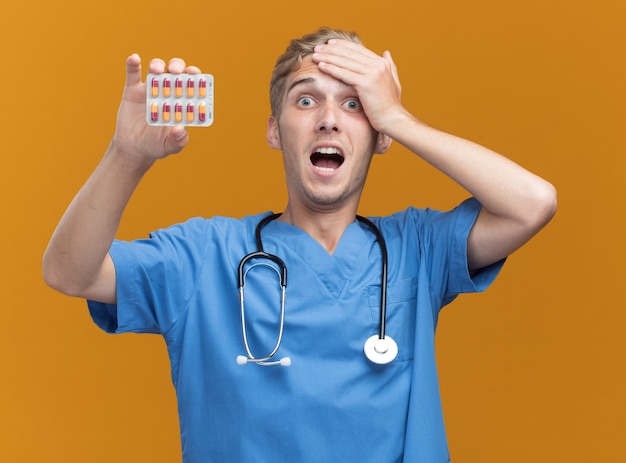 Przestraszony młody lekarz mężczyzna ubrany w mundur lekarza ze stetoskopem trzymając pigułki kładąc rękę na głowie na białym tle na pomarańczowej ścianie