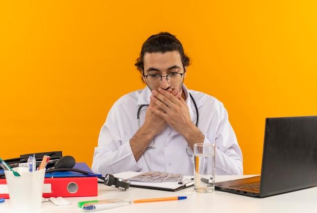 Przestraszony młody lekarz mężczyzna w okularach medycznych, ubrany w szatę medyczną ze stetoskopem, siedzący przy biurku
