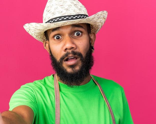Przestraszony młody ogrodnik afroamerykański facet w kapeluszu ogrodniczym, trzymający aparat