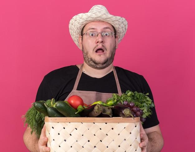 Przestraszony młody ogrodnik mężczyzna w kapeluszu ogrodnictwo trzymając kosz warzyw na białym tle na różowej ścianie