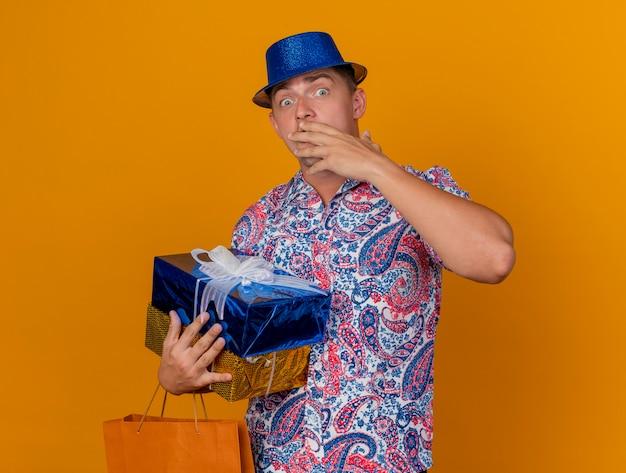 Przestraszony młody partyjny facet w niebieskim kapeluszu, trzymając pudełka z torbą zakrył usta ręką na białym tle na pomarańczowym tle
