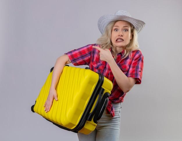 Przestraszony młody podróżnik na sobie czerwoną koszulę w kapeluszu trzymając walizkę wskazuje na bok na odizolowanej białej ścianie