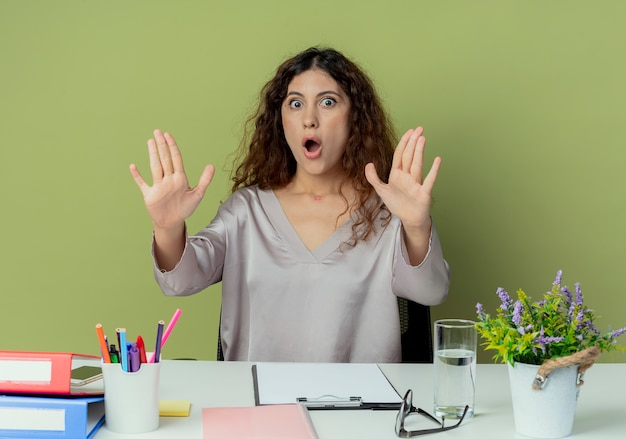 Przestraszony młody pracownik biurowy całkiem żeński siedzi przy biurku z narzędzi biurowych wyciągając ręce do kamery na białym tle oliwek
