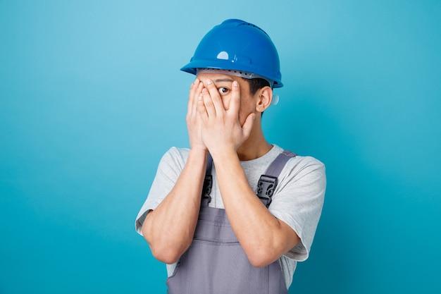 Przestraszony młody pracownik budowlany w kasku ochronnym i mundurze zakrywającym twarz rękami zerkając na aparat między palcami