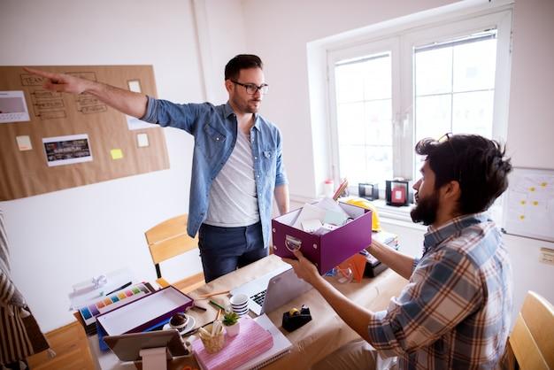 Przestraszony młody pracownik, siedzący na krześle i trzymający pudełko ze swoimi rzeczami po zwolnieniu, nieszczęśliwy, wściekły szef wskazuje w stronę, stojąc przed nim.