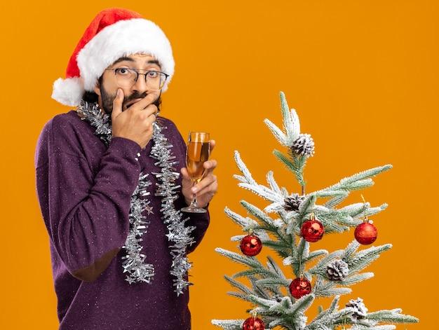 Przestraszony młody przystojny facet stojący w pobliżu choinki w świątecznym kapeluszu z girlandą na szyi trzymający kieliszek szampana zakryte usta dłonią odizolowaną na pomarańczowej ścianie