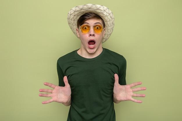 Przestraszony młody przystojny facet w kapeluszu w okularach