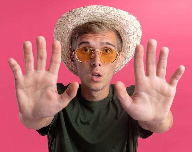 Przestraszony młody przystojny facet w zielonej koszuli i okularach z kapeluszem, wyciągając ręce z przodu na białym tle na różowej ścianie