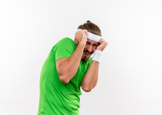 Przestraszony młody przystojny sportowy mężczyzna nosi opaskę i opaski na nadgarstek kładąc pięści na głowie patrząc na białym tle na białej przestrzeni
