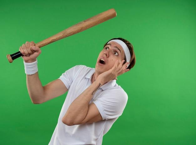 Przestraszony młody sportowy facet patrząc na sobie opaskę z nadgarstkiem trzymając kij baseballowy na białym tle na zielonej ścianie z miejsca na kopię