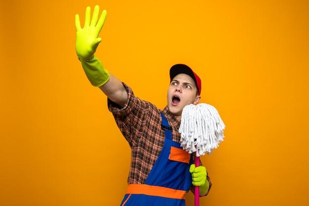 Przestraszony młody sprzątacz ubrany w mundur i czapkę z rękawiczkami, trzymający mop