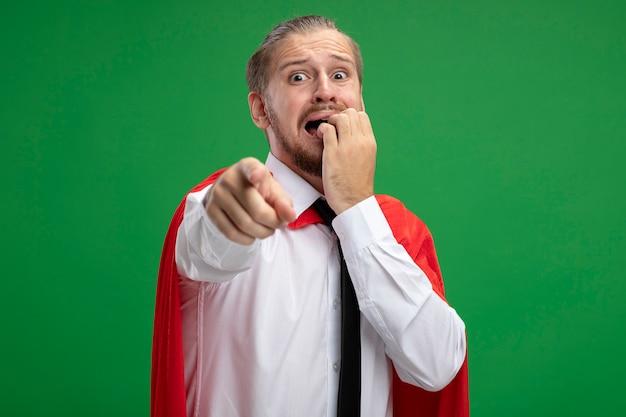 Przestraszony młody superbohater facet ubrany w krawat gryzie paznokcie punkty na aparat na białym tle na zielonym tle