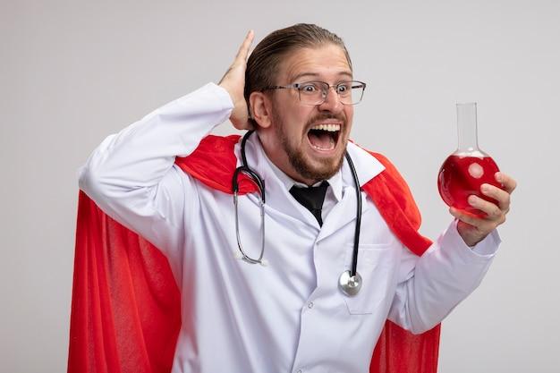 Przestraszony młody superbohater w szlafroku medycznym ze stetoskopem i okularami, trzymając i patrząc na szklaną butelkę chemii wypełnioną czerwonym płynem, kładąc rękę na głowie na białym tle