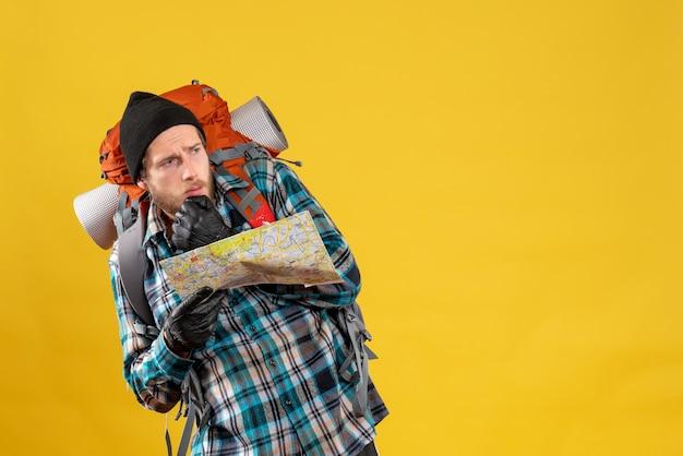 Przestraszony młody turysta w skórzanych rękawiczkach i plecaku trzymającym mapę