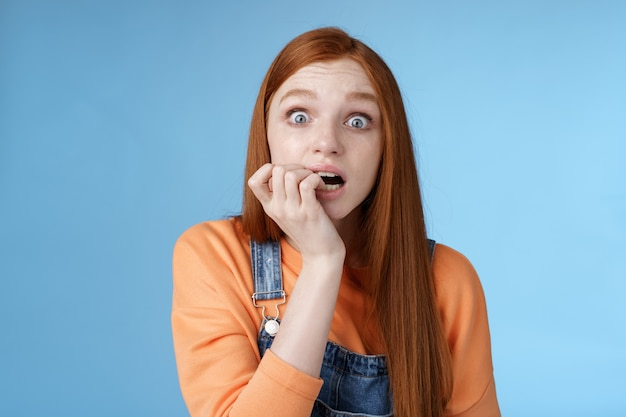 Przestraszony niepewny siebie niespokojny młoda drżąca ruda dziewczyna szeroko otwartymi oczami wpatrując się intensywnie emocjonalnie gryząc paznokcie fan martwi się ulubiona postać serialu telewizyjnego umiera stojąc nerwowo niebieskie tło