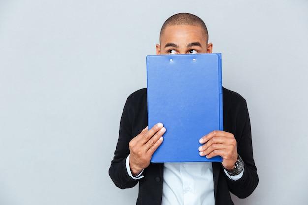 Przestraszony, nieśmiały młody człowiek z afryki, zakryty ukrytą twarzą z niebieskim folderem
