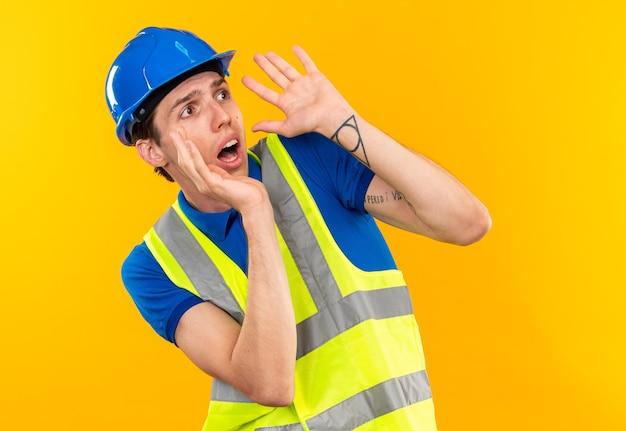 Przestraszony patrząc na bok młodego budowniczego mężczyzny w mundurze