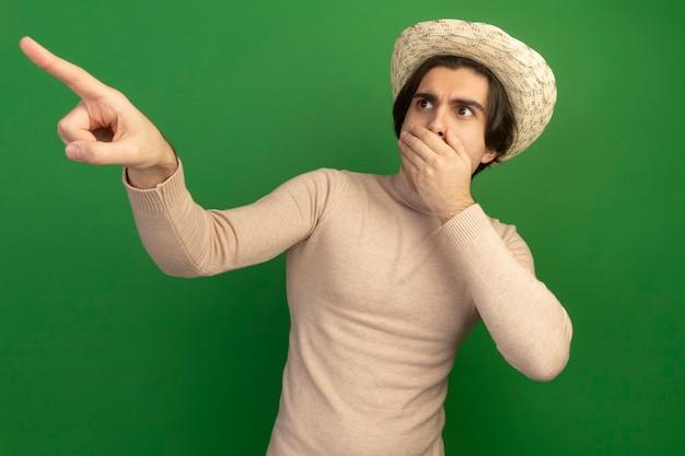 Przestraszony, patrząc na bok, młody przystojny facet w kapeluszu zakrytym ustami z punktami dłoni z boku na zielonej ścianie