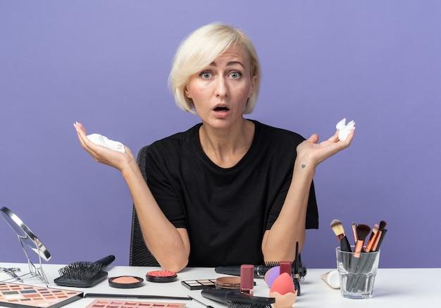 Przestraszony, patrząc na kamerę, młoda piękna dziewczyna siedzi przy stole z narzędziami do makijażu, trzymając krem do włosów na białym tle na niebieskim tle