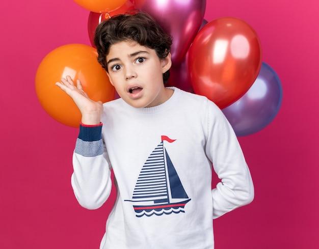 Przestraszony patrząc na małego chłopca stojącego z przodu balony rozkładające rękę na białym tle na różowej ścianie