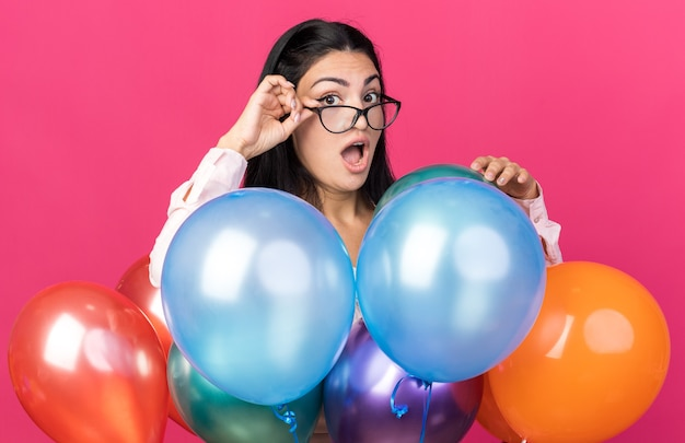 Przestraszony patrzący aparat młoda piękna kobieta w okularach stojąca za balonami odizolowanymi na różowej ścianie
