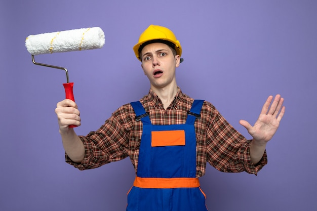 Przestraszony pokazując gest zatrzymania młody mężczyzna budowniczy ubrany w mundur trzymający szczotkę rolkową