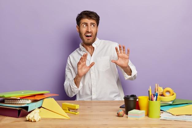 Przestraszony pracownik siedzi przy biurku