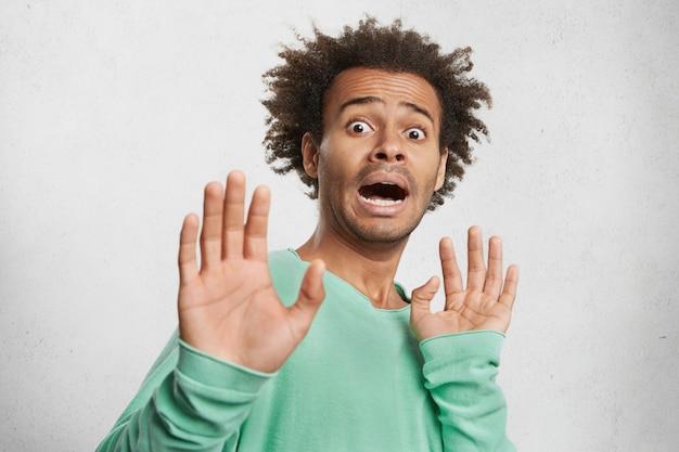 Przestraszony przerażony zmartwiony mężczyzna trzyma dłonie przed sobą, woła głośno, próbuje bronić się przed złodziejem,