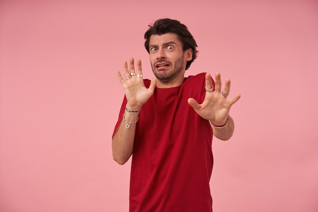 Przestraszony, przestraszony młody człowiek z włosiem w czerwonej koszulce, wykonujący przerażony gest dłońmi, próbując się bronić