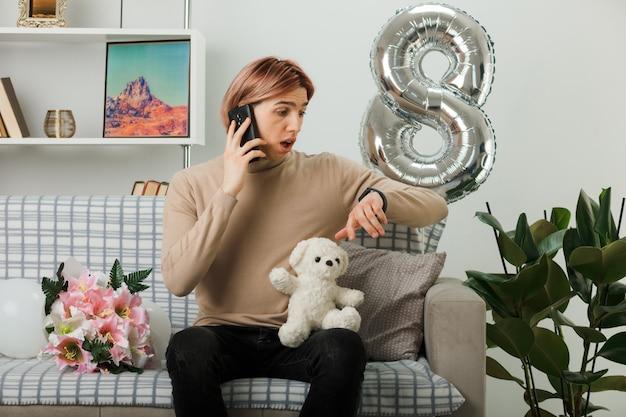 Przestraszony przystojny facet na szczęśliwy dzień kobiet trzymający pluszowego misia rozmawia przez telefon, patrząc na zegar na nadgarstku siedzący na kanapie w salonie