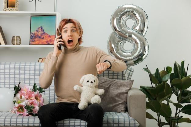 Przestraszony przystojny facet w szczęśliwy dzień kobiet trzymający pluszowego misia mówi przez telefon, siedząc na kanapie w salonie